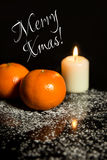 Tangerines and Candle on icing sugar, black stone and black back Stock Images