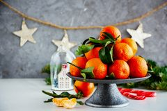 Tangerines and Christmas. Christmas decor and fresh raw tangerines citrus fruits with leaves - Image royalty free stock images