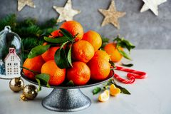 Tangerines and Christmas. Christmas decor and raw organic tangerines citrus fruits with leaves - Image stock image