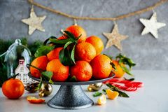 Tangerines and Christmas. Holiday. Fresh tangerines citrus fruits with leaves and Christmas decor - Image royalty free stock photography