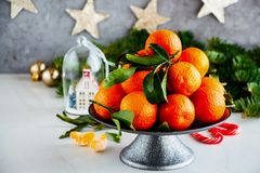 Tangerines and Christmas. Raw organic tangerines citrus fruits with leaves and Christmas decor - Image stock images