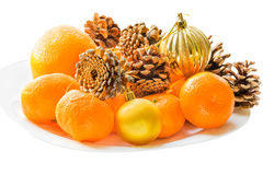Tangerines, cones, Christmas balls on a white plate Royalty Free Stock Photography