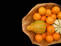 Tangerines and decorative pumpkins. In wooden bowl isolated on black background Royalty Free Stock Images