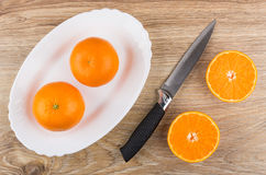 Tangerines in dish, half of tangerine and knife Stock Images