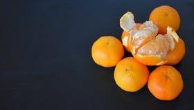 Tangerines em um fundo preto imagem de stock