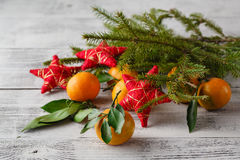 Tangerines, fir tree brunches, pine cones and nuts. Christmas fo Stock Images