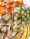Tangerines, grapes, bananas and potatoes in cellophane bags Royalty Free Stock Image