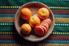 Tangerines i marchewka na earthen talerzu na jaskrawym tablecloth Zdjęcia Royalty Free