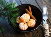 Tangerines jaskrawy pomarańczowy dojrzały z zielonymi liśćmi na szarość talerzu z jodłą rozgałęzia się na drewnianym stole boże n obrazy royalty free