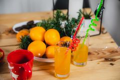 Tangerines, juice in glass cups and Christmas paraphernalia.  stock photo