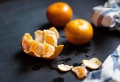 Tangerines kłamają na czarnym stole z pasiastym bieliźnianym ręcznikiem Obrazy Royalty Free