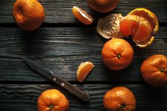 Tangerines with a knife on a wooden background. Healthy food. Fruit. A Royalty Free Stock Photo