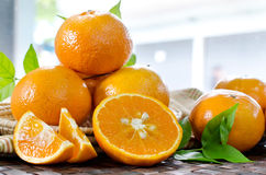 Tangerines with leaves in a beautiful basket, on wickerwork tabl Royalty Free Stock Images