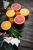 Tangerines with leaves in Christmas decor with Christmas tree, dry orange and candies over old wooden table Royalty Free Stock Photography