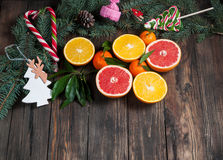 Tangerines with leaves in Christmas decor with Christmas tree, dry orange and candies over old wooden table. Rustic style. Top vie Royalty Free Stock Photos