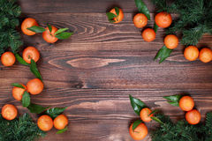 Tangerines with leaves and Christmas tree on wooden surface top view. Tangerines on old wooden table, close up Royalty Free Stock Images