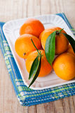 Tangerines with leaves in plate Royalty Free Stock Photos