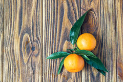 Tangerines with leaves on rustic wooden table with copy space. Top view. Close-up, horizontal Royalty Free Stock Photos