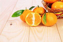 Tangerines with leaves on the table. Tangerines with leaves in the basket on the table Stock Photography