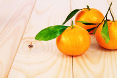 Tangerines with leaves on the table. Three tangerines with leaves on the table Royalty Free Stock Photography