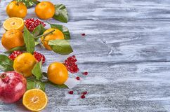 Tangerines with leaves on a wooden background stock photo