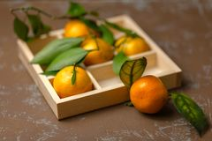 Tangerines with leaves in a wooden box. Natural vitamin royalty free stock photography