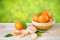 Tangerines with leaves in a wooden plate Royalty Free Stock Photography