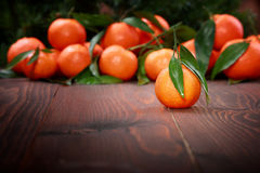 Tangerines with leaves on wooden surface Stock Photo