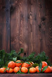 Tangerines with leaves on wooden surface. Citrus fruit Stock Photo