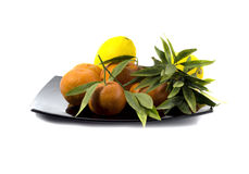 Tangerines with a lemon spread out on a black plate Stock Photos