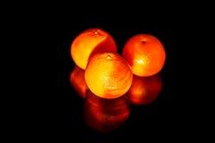 Tangerines lie on a black mirror. Royalty Free Stock Photos