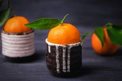 Tangerines lub clementines z zielonymi liśćmi na ciemnym drewnianym tle zdjęcie stock