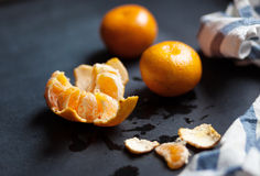 Tangerines are lying on the black table with a striped linen towel. Royalty Free Stock Images
