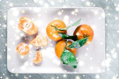 Tangerines, mandarines, clementines in winter holiday time, citrus fruits on plate with glowing snow and glitter on flatlay. Christmas, New Years Eve and food royalty free stock image