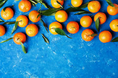 Tangerines or mandarins with green leaves on rustic blue table from above in flat lay style. Royalty Free Stock Image