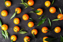 Tangerines or mandarins with green leaves on vintage black table from above in flat lay style. Royalty Free Stock Photography