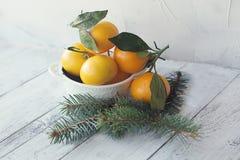 Tangerines mandarynka z liśćmi w białym talerzu na drewnianym tle z choinką zdjęcia stock