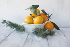 Tangerines mandarynka z liśćmi w białym talerzu na drewnianym tle z choinką obraz royalty free