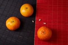 Tangerines mandarynki, clementines, cytrus owoc na stylowym czarnym i czerwonym tle z kopii przestrzenią fotografia stock