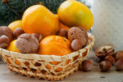 Tangerines and nuts in a wicker basket on the background of fir branches. Christmas. New year Stock Photos