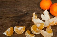 Tangerines, obrany tangerine i tangerine plasterki na drewnianym tle, Z kopii przestrzenią Zdjęcia Royalty Free