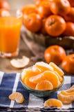 Tangerines, obrany tangerine i tangerine plasterki na błękitnym płótnie, Mandarine sok Fotografia Royalty Free