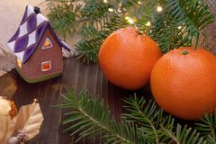 Tangerines and ornaments with christmas lights and fir branches. Tangerines clementines and ornaments with christmas lights and fir branches on wooden background royalty free stock images