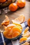 Tangerines, peeled tangerine and tangerine slices on a blue cloth. Mandarine juice Royalty Free Stock Photo