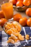 Tangerines, peeled tangerine and tangerine slices on a blue cloth. Mandarine juice Stock Image