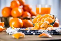 Tangerines, peeled tangerine and tangerine slices on a blue cloth. Mandarine juice Stock Photos