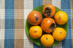 Tangerines and persimmons in the green plate on the table. Royalty Free Stock Images