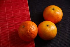 Tangerines in plate on black and red background. Tangerines with slices in plate on black and red background Royalty Free Stock Photos