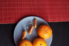 Tangerines in plate on black and red background. Tangerines with slices in plate on black and red background Royalty Free Stock Images