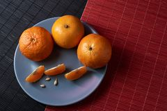 Tangerines in plate on black and red background. Tangerines with slices in plate on black and red background Royalty Free Stock Photography